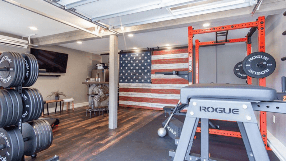 Home gym with Rogue Fitness equipment and an American Flag wood paneled wall