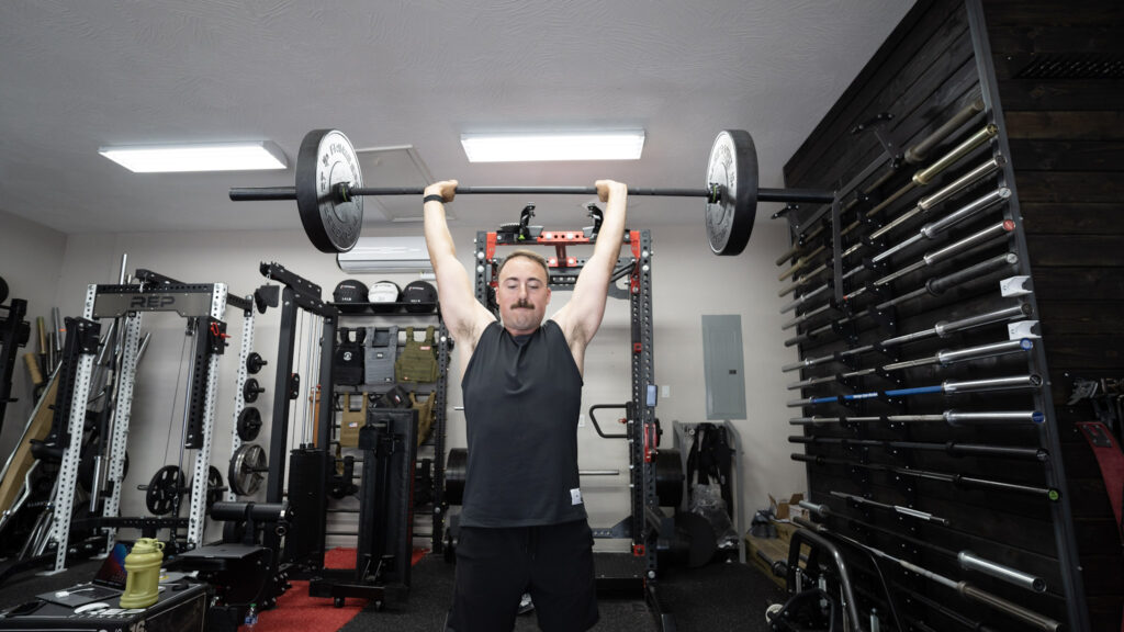 Man pressing a barbell with a 45-pound weight plate on each side overhead in a demonstration of one of the best barbell exercises.