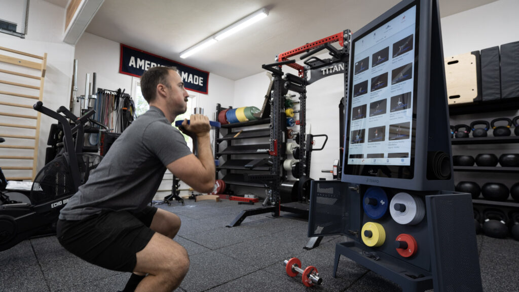 Coop squatting in front of the Tempo Studio during a smart home gym workout in his garage gym.