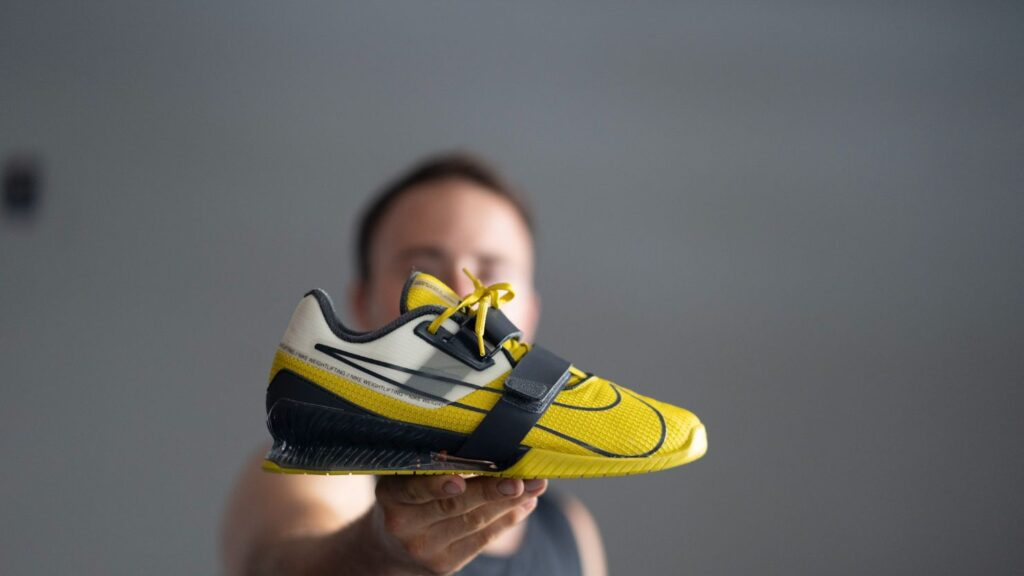 Man holding Nike Romaleos 4 weightlifting shoes to show side profile against a gray background