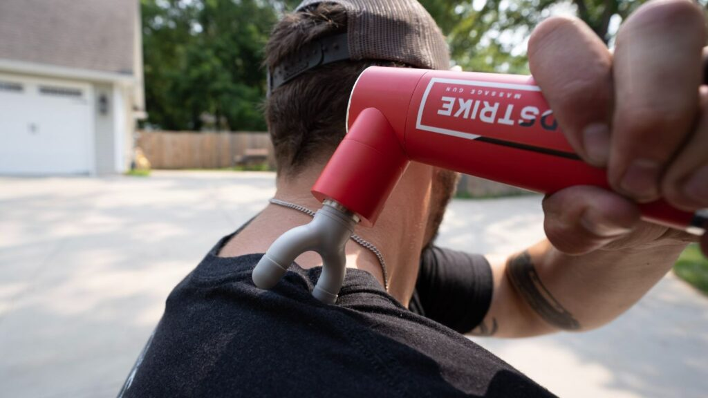 A man outdoors using the REP Rapidstrike massage gun with the fork attachment on his shoulder.