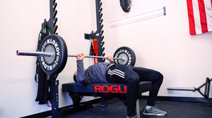 Man bench pressing weights in a home gym