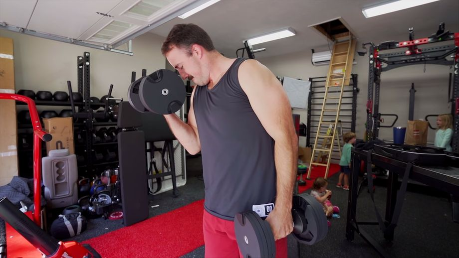 Coop doing dumbbell curls in a home gym