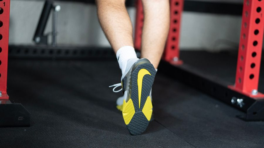 Closeup of the underside of Nike Savaleos weightlifting shoes showing the yellow Nike check mark.