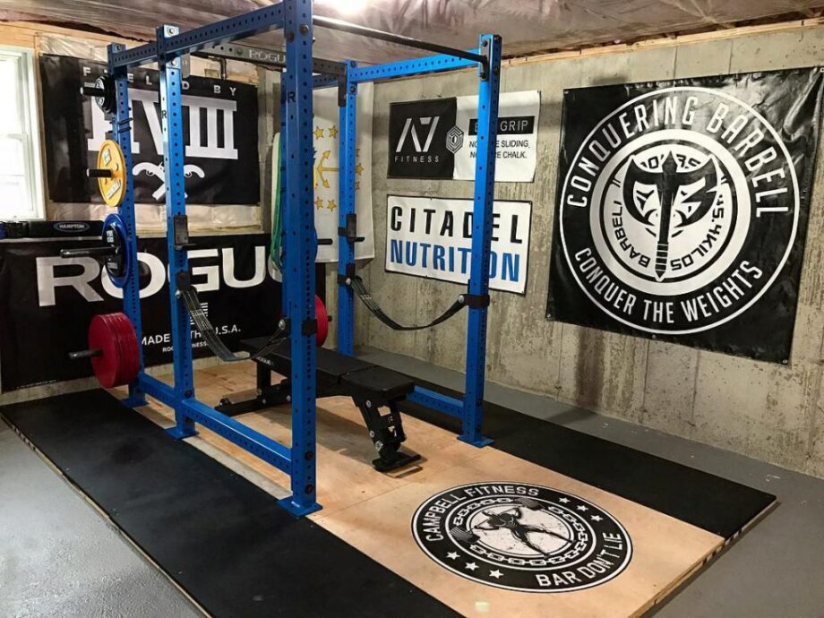 Home gym with a double squat rack and wooden platform.