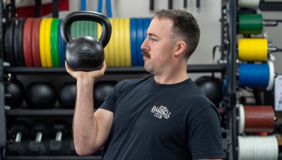 Man holding a kettlebell in a gym