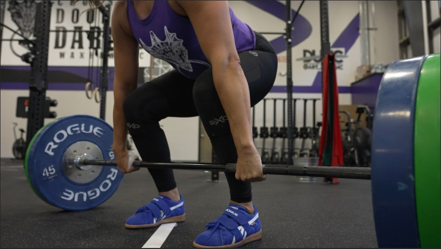 Woman deadlifting weights in a gym