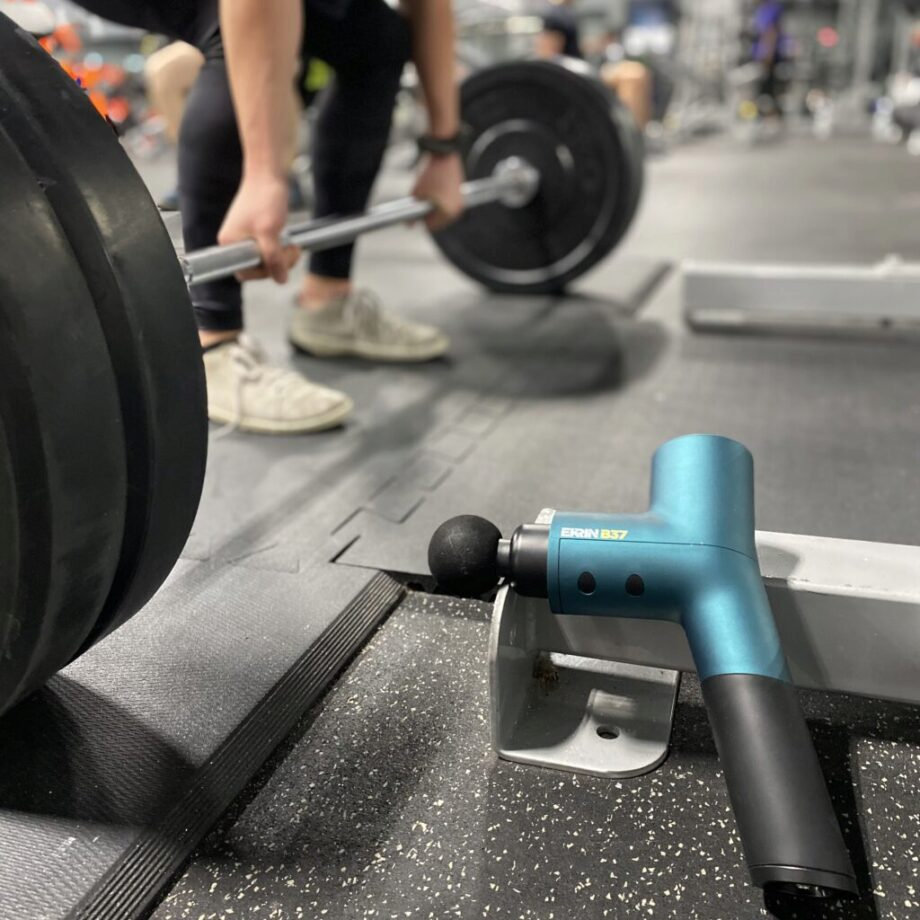 Ekrin Athletics b37 massage gun in focus while someone is doing deadlifts in the background
