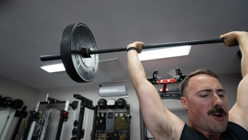 Coop lifting a barbell that has Fringe Sport Army Weight Plates