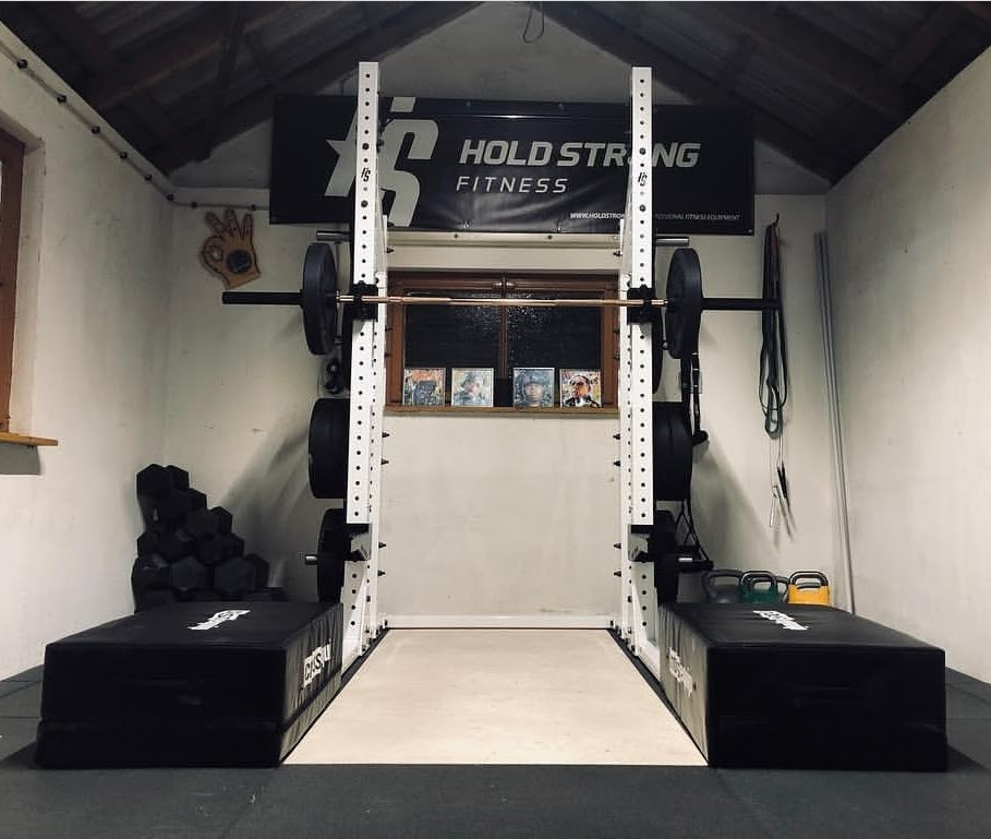 Simple home gym with a white squat rack, barbell and weight plates, and kettlebells.