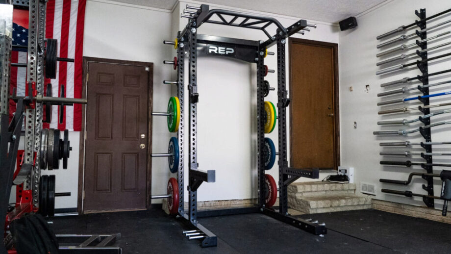 A home gym with a REP fitness rack, weight plates, and barbells.