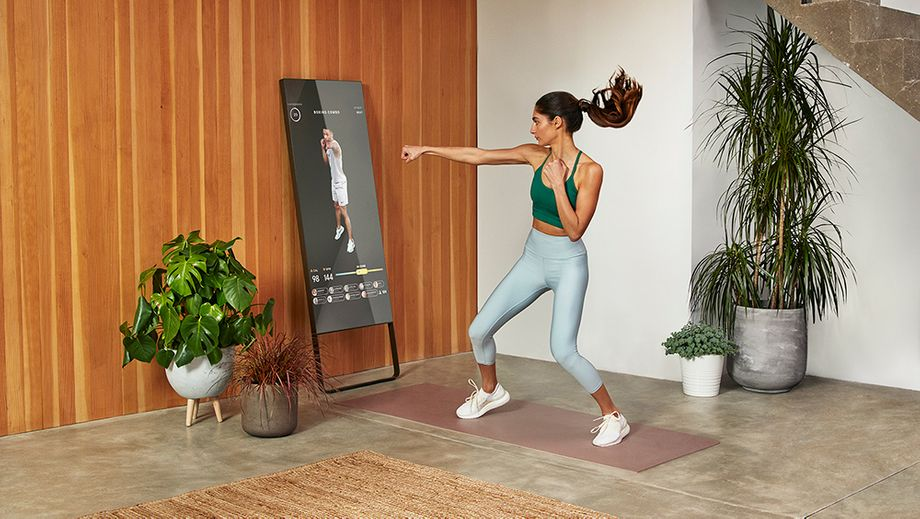 Product image of the mirror workout device with someone doing a boxing workout