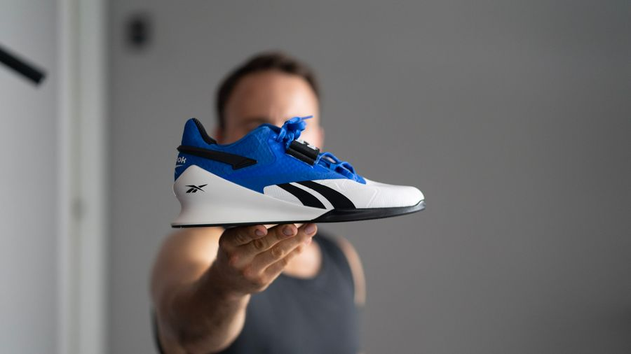 Man holding Reebok Legacy Lifter weightlifting shoes